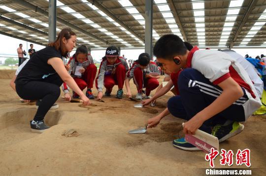 图为考古老师指导学生如何握拿手铲,从中体验考古发掘的过程究竟是怎样的。 周小云 摄
