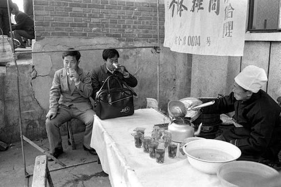 前门地区,北京大碗茶摊位。北京,1986年。[摄影:Guy Le Querrec]
