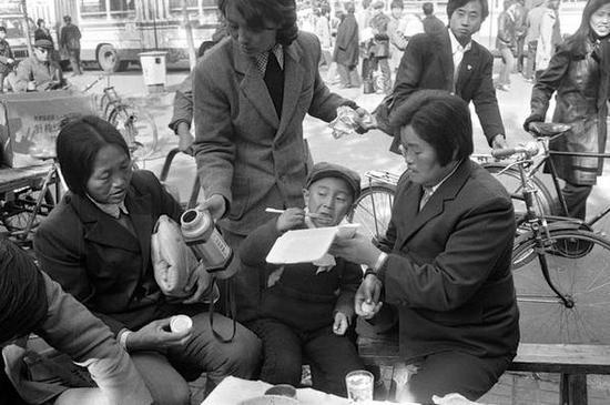 前门地区,吃盒饭的人们。北京,1986年。【摄影:Guy Le Querrec】