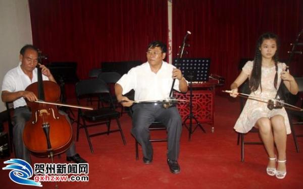 """图为""""三栖艺术家""""钟毓佑(中)与音乐爱好者演奏《赛马曲)"""